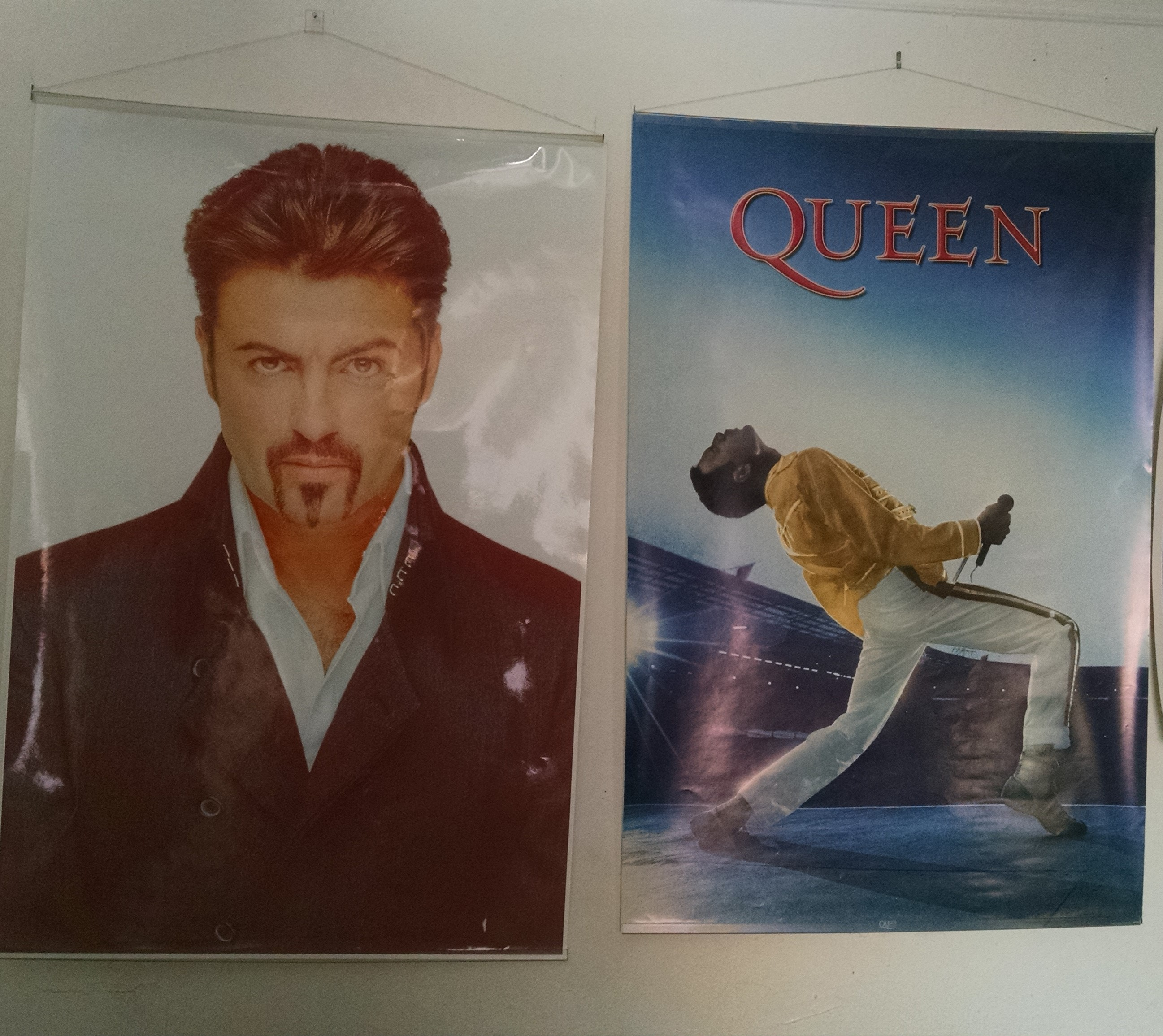 Image of a George Michael poster, and a Freddie Mercury poster, on the author's wall